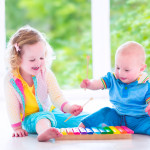 Two little children - cute curly toddler girl and a funny baby boy, brother and sister playing music, having fun with colorful xylophone at a window; kids early development class